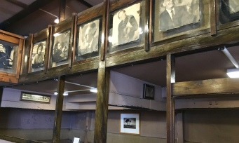 Wrinkled black and white portraits of musicians overpass wooden booths and shelves of vintage photograph