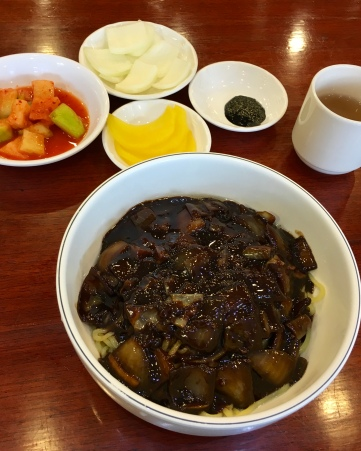 Jajangmyeon is always served with radish (Danmuji 단무지), sliced raw onion and accompanied with a small plate of Chunjang (춘장) sauce. Chunjang is the raw dark soybean paste which is made from roasted soy beans and a little bit of caramel