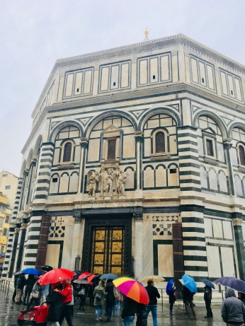 The Baptistery of St. John, Iconic octagonal basilica with striking marble facade, known for its bronze doors & mosaic ceiling