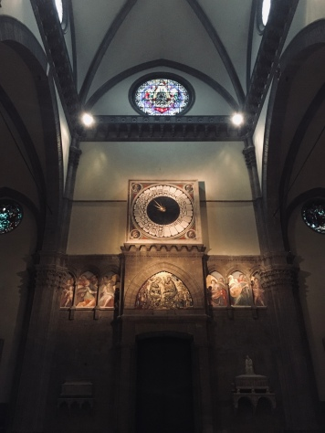 The clock above the main door inside the Cathedral of Santa Maria del Fiore. At its centre, a golden star decorates the blue disc of the clock's face, whilst the heads of what are believed to be the four evangelists, Matthew, Mark, Luke and John, are encircled at each corner of the dial's square frame