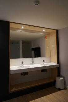 Big mirror with sink. Bathroom with a hot shower inside the room