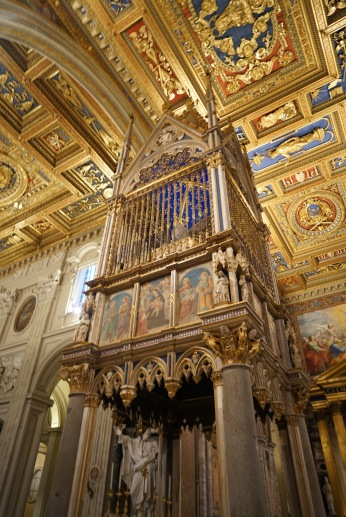 An elaborate Gothic baldachin stands over the papal altar. Dating to the 14th century, this towering ensemble is said to contain the relics of the heads of Peter and Paul. In front, a double staircase leads down to the Renaissance tomb of Pope Martin V